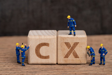 Customer Experience in product and service concept, miniature people workers with blue team uniform building cube wooden block with acronym CX on table with blackboard, user review or feedback