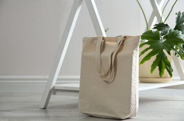 Eco bag and houseplant near white wall indoors. Space for design