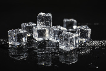 Pile of crystal clear ice cubes on black background