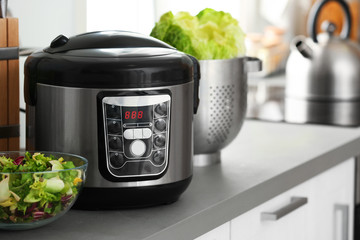 Modern electric multi cooker and food on kitchen countertop. Space for text