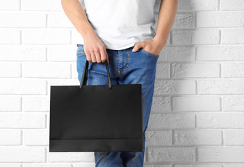 Man holding mock-up of paper shopping bag against wall