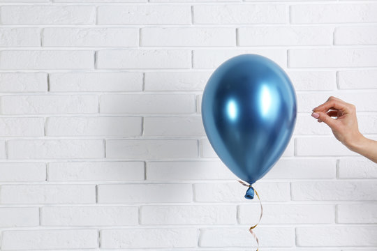Young woman piercing bright balloon near brick wall, space for text