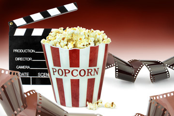 Popcorn, movie clapper and film strips.  Cinema concept image