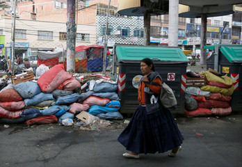 A woman walks past accumulated rubbish after a landslide took place at a landfill in La Paz