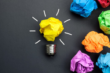 Great idea concept with crumpled colorful paper and light bulb on black background