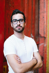 Portrait Of Young Handsome Man wearing glasses,  moustache and beard  Outdoor on red wall background