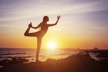Female yoga silhouette on sea sunset