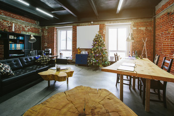 Christmas tree in modern Loft Office interior. Wooden decoration tables, red brick wall