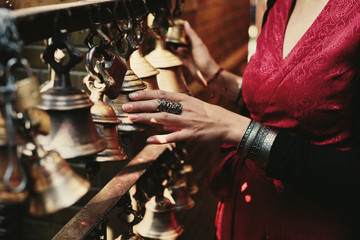 Woman hand touching buddhist bells in Nepali temple