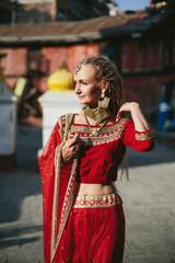 European woman wearing dreadlocks and Indian red dress