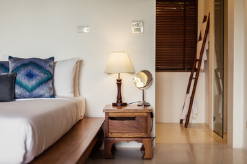 Modern bed room interior in Luxury villa. White colours, lamp, enter to bathroom