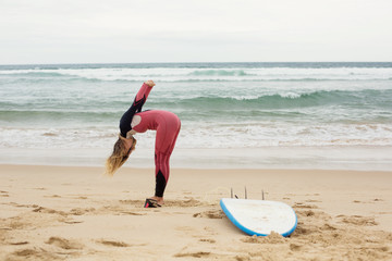 Happy funny positive female surfer with surf board on ocean beach doing exercises