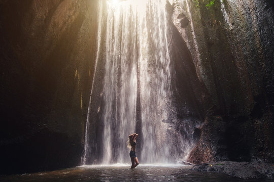 Woman enjoying in tropical waterfall