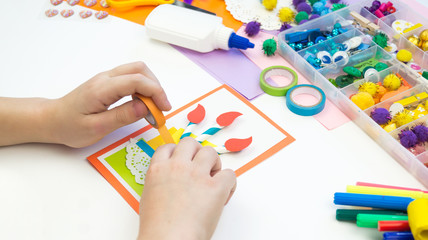 Child makes a postcard with a picture of a cake. Kid paperwork.