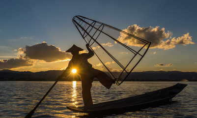 traditional Intha fisherman in long boat in the evening on Lake Inle