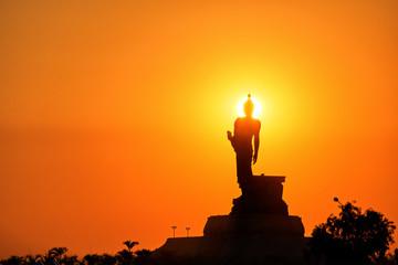 Silhouette Buddha statue on golden sunset background : Khon Kaen, Thailand