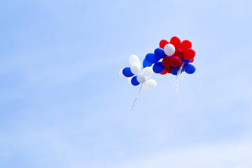 Multicolored balloons fly in the blue sky.