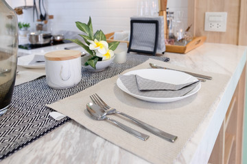 Set of modern dining table with white plate, spoon and fork near flower on marble table. Interior design for decoration home.