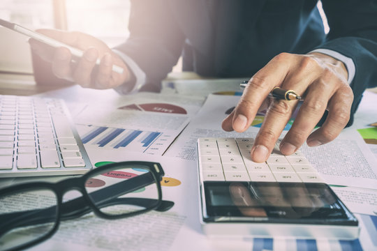 Businessman or accountant working on calculator to calculate business data concept. Accounting,investment advisor consulting situation on the financial report and planning a marketing plan at office..