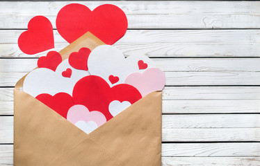 Valentine day minimal concept, hanmade gift - craft envelope with pink, red and white paper hearts on gray wooden background. Love concept.