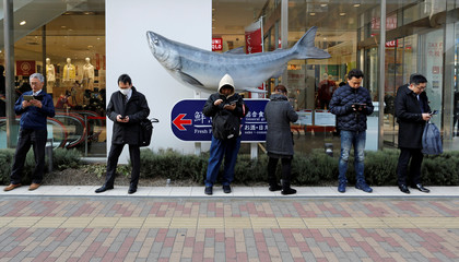 People use their smartphones on the street in Tokyo