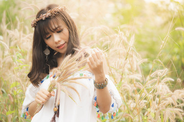 Summer portrait of young Asian hipster woman or hippie style in a grass on sunny day,Fashion vintage, Bohemian fashion, concept. trendy clothes. trendy clothes. Soft warm vintage color tone.