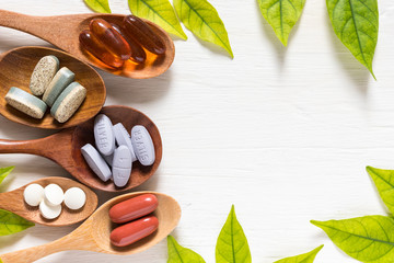 Fototapeta Variety of vitamin pills in wooden spoon on white background with green leaf, supplemental and healthcare product, flat lay surface obraz