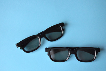 Two black plastic glasses on a blue background. Sunglasses, 3D glasses for the cinema.