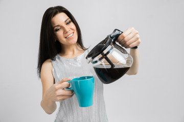 young girl with a coffee pot and a mug stands isolated on a light background