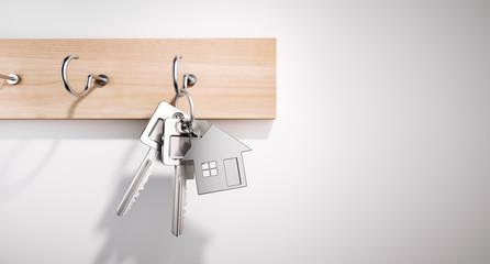Schlüsselbrett mit Schlüsseln und Haus vor heller Wand
