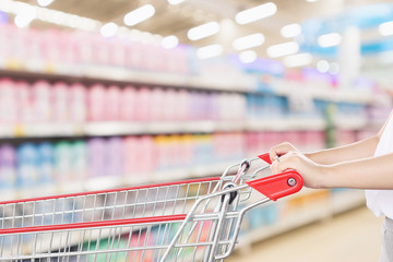Woman hand hold empty red shopping cart with abstract blur supermarket discount store with body care cosmetic shelves interior defocused background