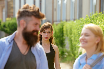 Totally jealous of him. Bearded man cheating his girlfriend with another woman. Jealous woman look at couple in love on street. Unhappy girl feeling jealous. Romantic couple of man and woman dating