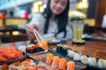 Asian lady eat a Salmon fish sashimi and Sushi in Japanese restaurant