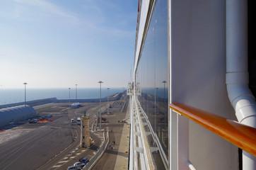 Blick von Kreuzfahrtschiff auf Hafenanlage mit Spiegelung in Fensterfront
