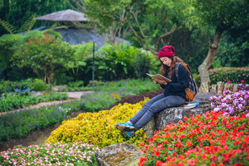 woman travel nature in the flower garden. relax sitting on rocks and reading books In the midst of nature at national park doi Inthanon...