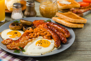 Full English breakfast, with sausage, mushrooms, beans and a fried egg.
