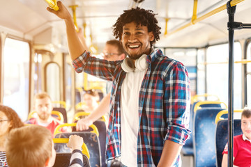 Young smiling African American man riding in the city bus and looking at camera.