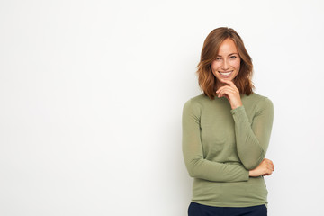 portrait of a young happy woman smiling and thinking on white background looking in camera