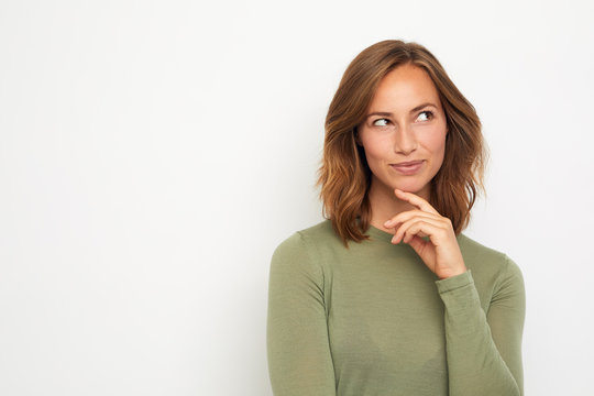 portrait of a young happy woman smiling and thinking on white background