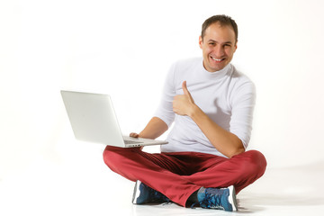 Happy young man sitting on a floor and using laptop isolated over white background