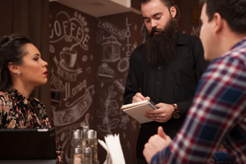Waiter taking order from stylish couple in restaurant Hipster restaurant.