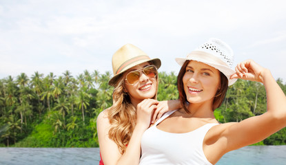 travel, tourism and summer vacation concept - young women or teenage girls in hats over infinity edge pool and palms in sri lanka background