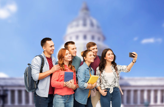 education, high school and technology concept - group of smiling students with books taking selfie by smartphone over capitol building background