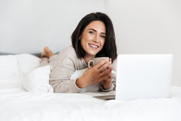 Photo of middle-aged woman 30s using laptop, while lying in bed with white linen in bright room