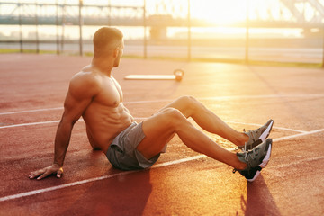Muscular shirtless Caucasian sporty man sitting on the court and resting from exercises, looking at morning sun.