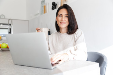Image of attractive woman 30s working on laptop, while sitting over white wall in bright room