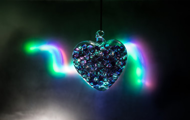 Valentines Day Concept. Glass transparent heart on dark. Crystal heart in the dark, glass heart glows, glass painting, black background