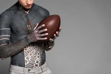 cropped shot of bare-chested man with tattoos holding rugby ball isolated on grey