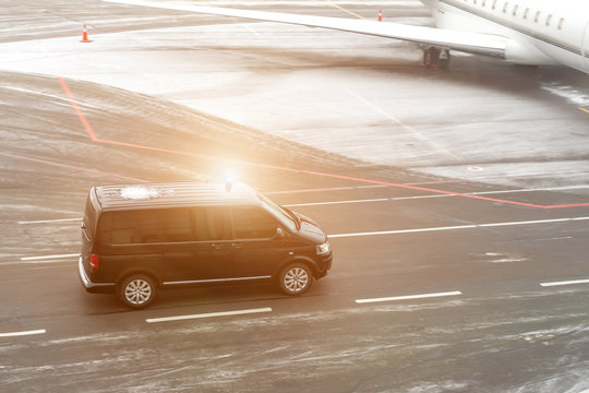 Black VIP service van running on airport taxiway with blurred private jet on background. Business class service at airport. Security intelligence agency hurrying at airfield