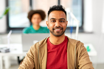 business and people concept - happy smiling indian man at office